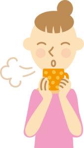 熱い飲み物を冷ますためにフーフーしている女性